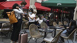 Una cameriera controlla il pass sanitario dei clienti in un ristorante a Parigi