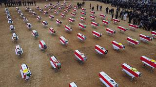 An aerial picture shows mourners gathering around coffins wrapped with the Iraqi flag during a mass funeral for Yazidi victims of the Islamic State (IS) group