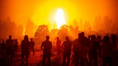 Local people gather during a wildfire next to the village of Kamatriades on Greece's Evia island on August 9, 2021