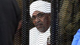 الرئيس السوداني المخلوع عمر البشير ينظر من قفص المدعى عليه خلال افتتاح محاكمة فساد في الخرطوم.