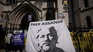 Supporters of WikiLeaks founder Julian Assange hold up a banner as they protest, during the first hearing in the Julian Assange extradition appeal, at the High Court in London