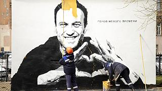 Municipal workers paint over graffiti of Russia's imprisoned opposition leader Alexei Navalny in St. Petersburg, Russia, Wednesday, April 28, 2021