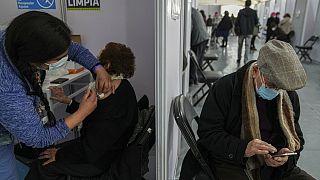 Una anciana recibe la tercera dosis de la vacuna contra la COVID-19 en el Estadio del Bicentenario de Santiago