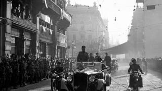FILE: Italian dictator Benito Mussolini, standing in his car, drives through the streets of Milan, on Oct. 30, 1936.
