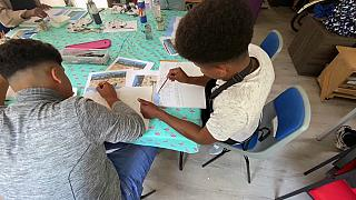 Children refugees painting and drawing at an art class in Folkestone, England.