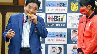 Nagoyas Bürgermeister Takashi Kawamura, links, beißt in die olympische Goldmedaille von Miu Goto, rechts, vom japanischen Softball-Team, 04.08.2021