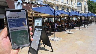 رجل يعرضُ الشهادة الصحية الرقمية المحمّلة على هاتفه الذكي أمام أحد المطاعم في فرنسا.