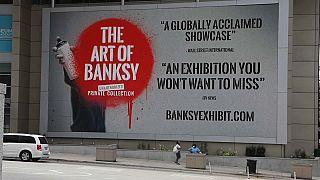 Il cartellone che pubblicizza la mostra di Banksy a Chicago.