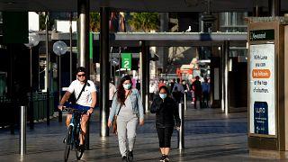 أشخاص يسيرون على  إمتداد ميناء سيدني حيث أعلنت أكبر مدينة في أستراليا قيوداً أكثر صرامة لمواجهة الجائحة. السبت 14 آب / أغسطس 2021
