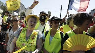 Demonstrators wearing yellow vests march in Paris on Saturday, Aug. 14, 2021.