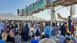 الأفغان يحتشدون في مطار كابل بينما يقف الجنود الأمريكيون في المدرج، أفغانستان، 16 أغسطس 2021.