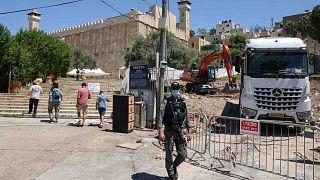 ضابط أمن إسرائيلي يقف حارسا أثناء قيام حفارة بأعمال البناء بجوار المسجد الإبراهيمي في مدينة الخليل المقسمة في الضفة الغربية المحتلة، 15 أغسطس 2021