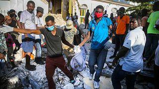 أشخاص يحملون جثة انتشلت من تحت أنقاض زلزال دمر منزله في ليس كاي، هايتي، الأحد 15 أغسطس 2021