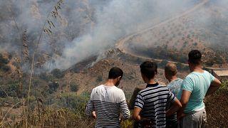 سكان يشاهدون حريقًا بالقرب من قرية توجة بمنطقة القبائل شرقي الجزائر العاصمة، الجمعة 13 أغسطس 2021