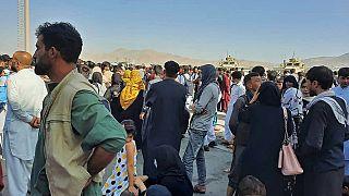 Des Afghans se pressent sur le tarmac de l'aéroport de Kaboul.