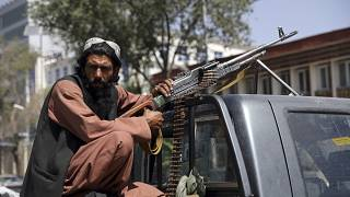 A Taliban fighter sits on the back of a vehicle with a machine gun in front of the main gate leading to the Afghan presidential palace, in Kabul, Afghanistan.