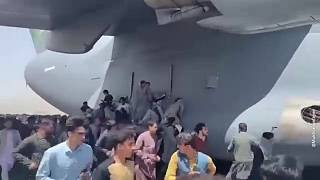 Afghans cling to a departing US military plane
