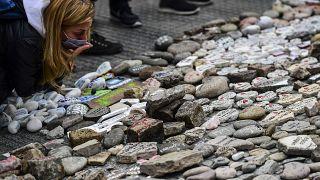 Egy nő megpuszilja elvesztett szerettének a nevével ellátott követ