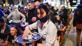 A waitress serves drinks at tables outside a pub in Soho, London as COVID-19 restrictions are eased on April 12, 2021.