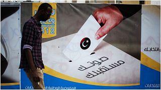 صورة أرشيفية لرجل ليبي يمر من أمام لوحة إعلانات للمفوضية العليا للانتخابات في 19 أيار/مايو 2012 في طرابلس