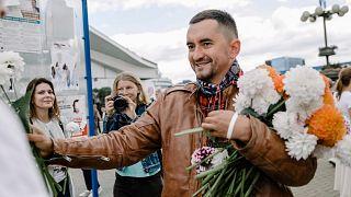 Szcjapan Latipau virágokat oszt egy tüntetésen Minszkben 2020. augusztus 12-én