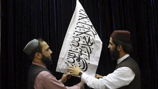 Oficiales talibanes arreglan la bandera blanca con la shahada, antes de la conferencia de prensa en Kabul, Afganistán, el 17 de agosto de 2021.