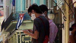 Un joven consulta su teléfono móvil en una calle de La Habana.