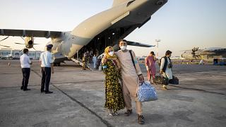 People evacuated from Afghanistan pose in front of a German Bundeswehr airplane after arriving at the airport in Tashkent, Uzbekistan, Aug. 17, 2021.