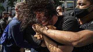 Civil ruhás rendőrök őrizetbe vesznek egy kormányellenes tüntetőt a magas árak, élelmiszerhiány és áramkimaradások miatt tartott tüntetésen, július 11-én