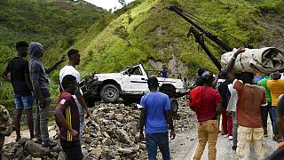 A crane removes a truck from a pile of rocks after landslides triggered by a 7.2-magnitude earthquake that hit four days prior in River Glass, Haiti, Wednesday, Aug. 18, 2021.