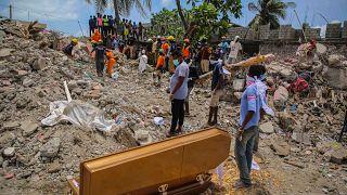 Emberek állnak a földrengés egyik halálos áldozatának a koporsója mellett, akinek holttestét a romok alatt találták meg