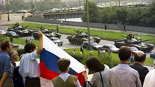Protesters gather at the Russian Government building holding a Russian national flag to oppose the oncoming line of tanks around the building in Moscow, August 19, 1991.