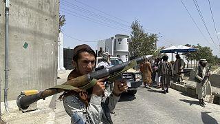 Un guerrigliero talebano di guardia davanti alla sede del ministero dell'Interno a Kabul, 17 agosto 2021