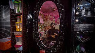 عاملة جنس تضع مساحيق التجميل أثناء جلوسها أمام مرآة في منزلها في دولاتديا في بنغلادش.
