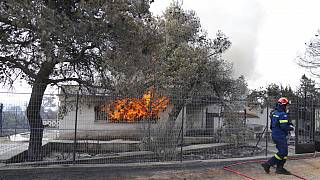 A firefighter extinguish the fire to a house during a wildfire in Thea area some 60 kilometers