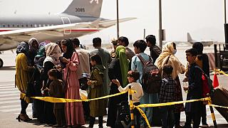 Civilians prepare to board an evacuation plane out of Kabul Airport.