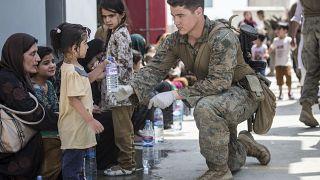 Американский солдат предлагает воду ребенку в аэропорту Кабула