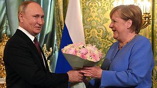 الرئيس الروسي فلاديمير بوتين  يرحب بالمستشارة الألمانية أنجيلا ميركل بباقة من الزهور خلال اجتماعهما في الكرملين في موسكو في 20 أغسطس 2021.
