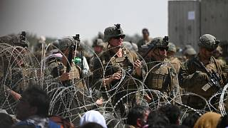 US soldiers stand guard behind barbed wire near Kabul airport, 20 August 2021
