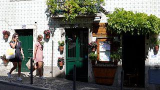 Portekiz'in başkenti Lizbon'da bir kafenin önünden geçen kadınlar