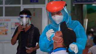 A medical worker takes swab sample from a man in Vung Tau city, Vietnam Saturday, Aug. 21, 2021.