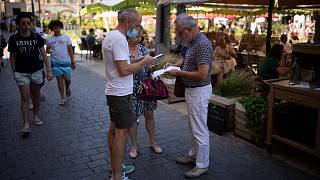 A restaurant owner scans a health pass at a restaurant in Marseille, southern France, Monday, Aug. 9, 2021.