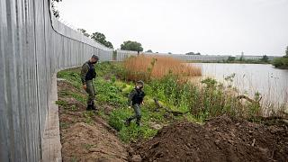 In this May 21, 2021, file photo, policemen patrol alongside a steel wall at Evros river, near the village of Poros, at the Greek -Turkish border, Greece.