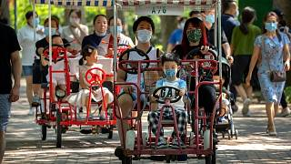Adults and children ride pedal cycles at a public park in Beijing, Saturday, Aug. 21, 2021.