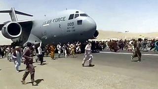 مئات الأشخاص يركضون جنباً إلى جنب مع طائرة نقل تابعة للقوات الجوية الأمريكية أثناء تحركها على مدرج المطار الدولي في كابول - 16 آب / أغسطس 2021