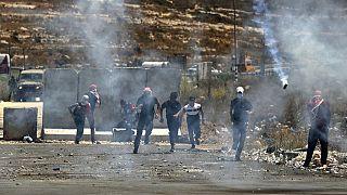 فلسطينيون يهرعون لتجنب قنابل الغاز المسيل للدموع  خلال مظاهرة في 17 أغسطس 2021