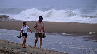 """Promeneurs sur la plage de Montauk (Etat de New York, USA), devant une mer de plus en plus agitée à l'approche de l'ouragan """"Henri"""", le 21/08/2021"""