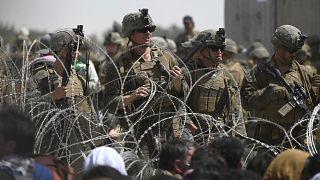 جنود أميركيون يقفون خلف أسلاك شائكة خلفها أفغان فروا لمطار كابول أملا في الخروج من أفغانستان بعد سيطرة طالبان على البلاد. 20/08/2021
