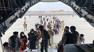 Katonák segítenek beszállni a menekülő embereknek egy szállító repülőgépbe a kabuli repülőtéren 2021. augusztus 18-án