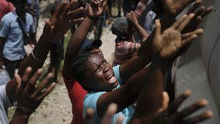Des haïtiens attendent une distribution d'eau à Cayes, le 22 août 2021